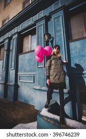 attractive blonde  girl is walking on a sunny day  outdoor with pink balloons. denim wall