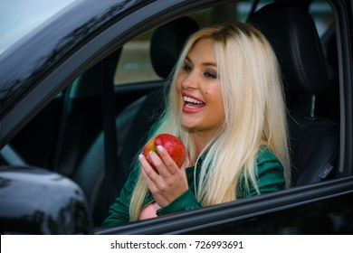 Attractive blonde hair woman in the car. Concept of woman and automobile. Adventures and problems on the roads