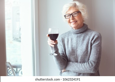 Attractive blonde haired old woman standing near window with wine
