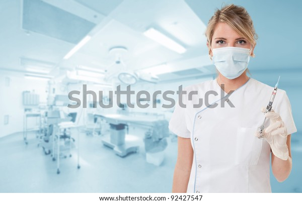 Attractive blonde holding a syringe in an operating room
