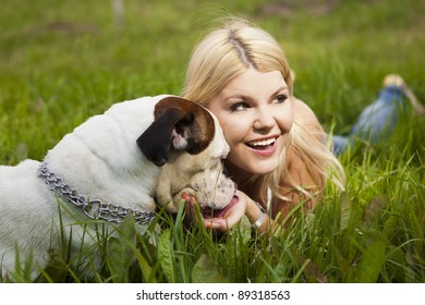 Attractive blonde plays with her dog, a boxer