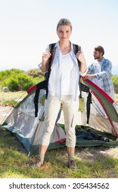 Attractive blonde smiling at camera while partner pitches tent on a sunny day