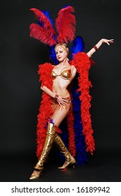 attractive blonde in stage costume over dark background