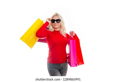 Attractive blonde with sunglasses with colorful bags on cutout white background