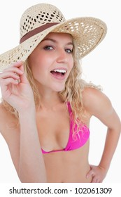 Attractive blonde teenager holding her hat brim against a white background