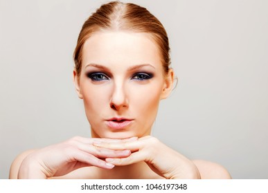 Attractive blonde topless woman with dark eye make up.