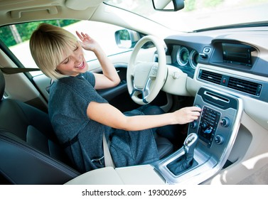 attractive blonde woman changing radio station in her car
