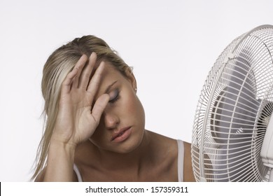 An attractive blonde woman with a deep tan cools off in front of an electric fan in hot weather.
