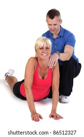Attractive blonde woman doing exercises with the support of her fitness coach.