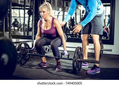 Attractive blonde woman doing trap bar deadlift exercise with help of her personal trainer. Toned image.