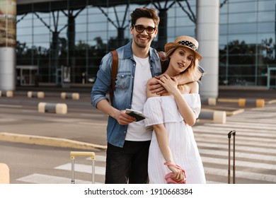 Attractive blonde woman in hat, white dress holds pink camera. Handsome brunette man in denim jacket hugs girlfriend and holds passport near airport.