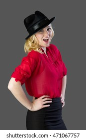 Attractive blonde woman having fun posing in front of a camera with a fedora
