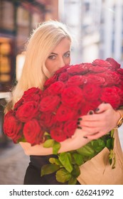 Attractive blonde woman keeps big bouquet of red roses in hands and sniffs it, on the street