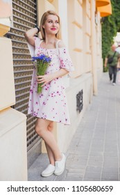 Attractive blonde woman in light pink dress with bouquet of cornflowers on the city streets. Stylish girl street fashion look, spring outfit