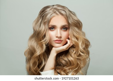 Attractive blonde woman with long healthy hair on white background