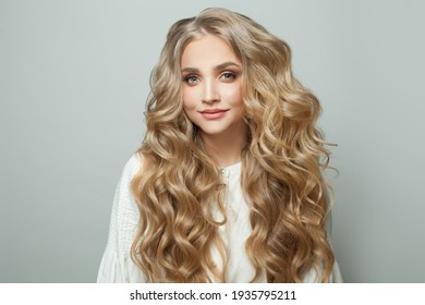 Attractive blonde woman with long perfect hair looking at camera and smiling on white background