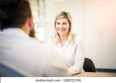 Attractive blonde woman model talking to salesman in the modern dealership while sitting at the table.