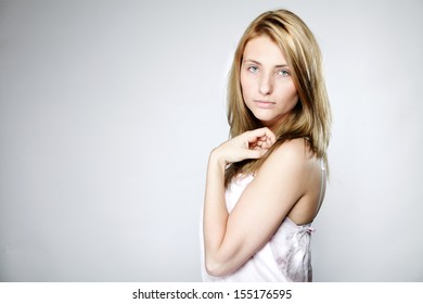 Attractive blonde woman with no make up gray background copy space