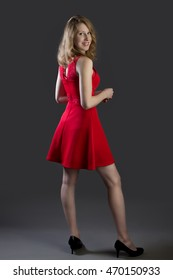 An attractive blonde woman in a red dress