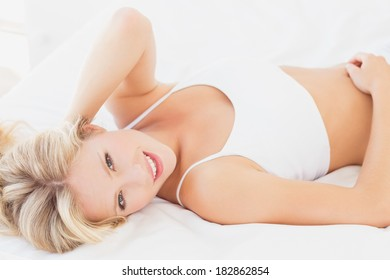 Attractive blonde woman relaxing on bed smiling at camera at home in the bedroom