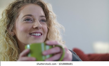 Attractive blonde woman sitting with coffee cup engaged in conversation.