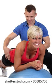 Attractive blonde woman undergoing some abdominal strengthening training on a gym ball.