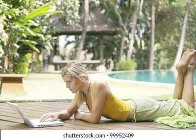 Attractive blonde woman using a laptop computer while laying down on a wooden deck in a tropical garden.