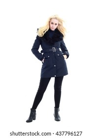 attractive blonde woman wearing dark winter coat with fur collar, standing pose. isolated against white background.