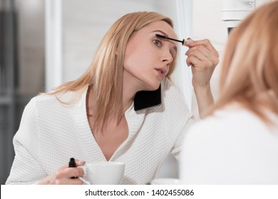 Attractive blonde woman in white bathrobe stands in bathroom by mirror. Applies makeup, speaks on mobile phone and drinks coffee. Morning fees, no time, doing lot of action at same time, multitasking.