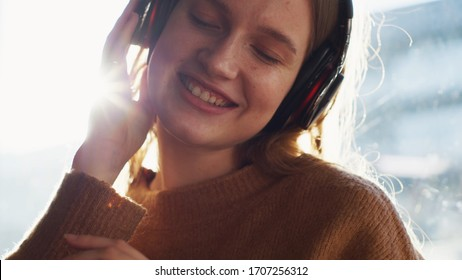 Attractive blondehair young woman with headphones near the window, relaxing, listenig and singing a favourite song with eyes closed and smiling at home. Rays of the sun Close up