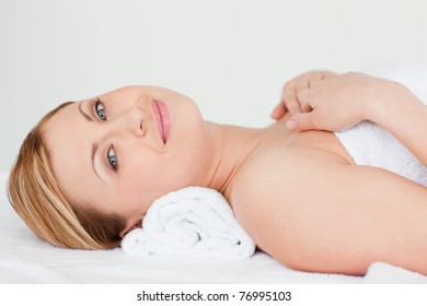 Attractive blond-haired woman lying down while receiving a spa treatment