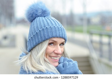 Attractive blue eyed blond woman in matching blue warm winter fashion wearing a knitted hat, scarf and gloves smiling at the camera