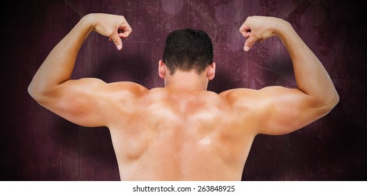 Attractive bodybuilder against red paint splashed surface