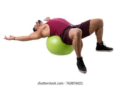 Attractive bodybuiler man exercising abs on an exercise ball in studio shot, isolatedo on white