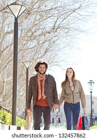 Attractive bohemian couple holding hands and walking together carrying shopping bags while on vacation in a destination city.