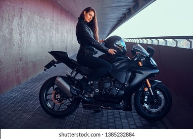 Attractive brave woman is sitting on her motobike in tunnel. She is holding helmet.