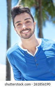 Attractive brazilian guy with palms and blue sky in the background