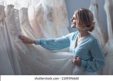 Attractive bride choosing a wedding dress in the store