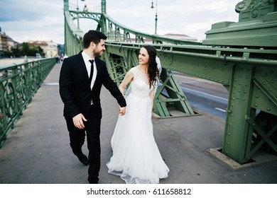 Attractive bride with curly hair and bridegroom standing close to each other on bridge, wedding photo, beautiful couple, Budapest city, portrait.