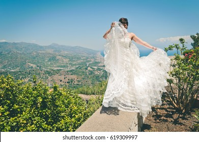 attractive bride just married, posing in elegant white wedding dress in a beautiful old village in Sicily on the seaside