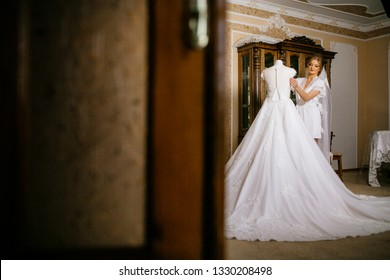 Attractive bride in white robe, long veil standing near the wedding dress on the mannequin on wedding morning. Preparing for the ceremony