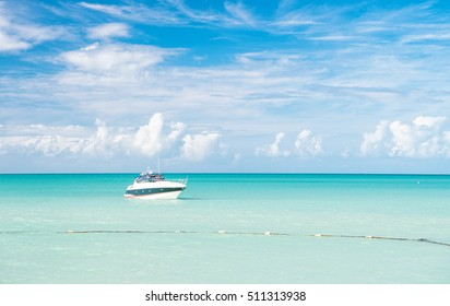 Attractive bright view of exotic colorful beautiful marine beach of Antigua St. Johns with boat on blue water and sky with small clouds in sunny weather outdoor on natural background, horizontal photo