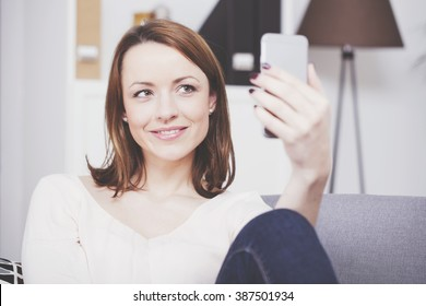 Attractive brown haired girl sitting on a sofa having a video call or taking a selfie