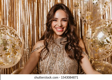 Attractive brown-eyed girl in shiny top looking at camera with smile on gold background