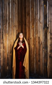Attractive brown-haired woman pray near wooden wall