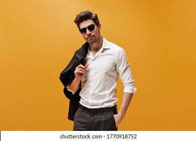 Attractive brunet man in stylish white shirt and trendy sunglasses poses on orange background and holds black jacket.