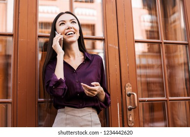 Attractive brunette asian businesswoman talking on mobile phone with client. Confident and succesfull worker, call manager, operator, communication online