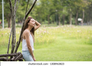 Attractive brunette Asian woman breathe fresh air for refreshment in greenery park and close eyes to relax. Portrait girl in summer or spring with copy space for text.
