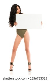 Attractive brunette with blank board in one piece swimsuit on white background