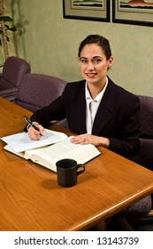 Attractive brunette business woman at her desk, with a cup of coffee.
